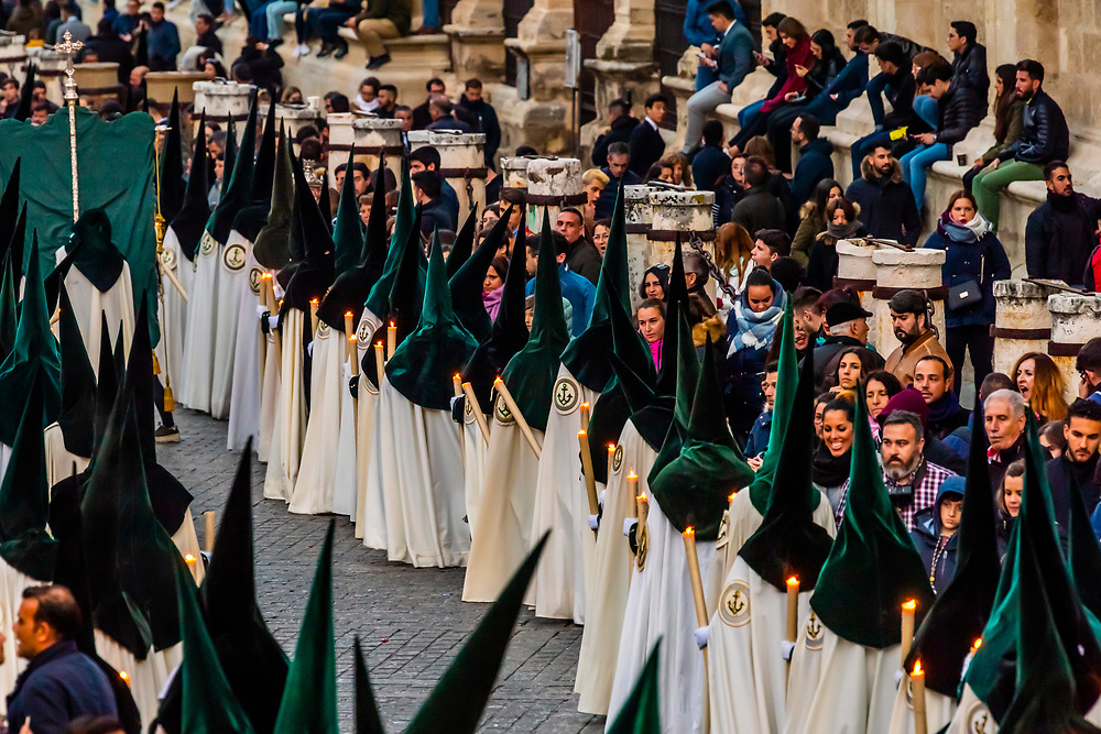 The procession of the Brotherhood (Hermandad) La Esperanza de Triana included hooded penitents (nazarenos) winds around the Seville Cathedral predawn on Good Friday, Holy Week (Semana Santa), Seville, Andalusia, Spain.