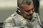 A New York City Police officer covered in ash from the World Trade Towers collapse tries in vein to use his radio on 09/11/01.
