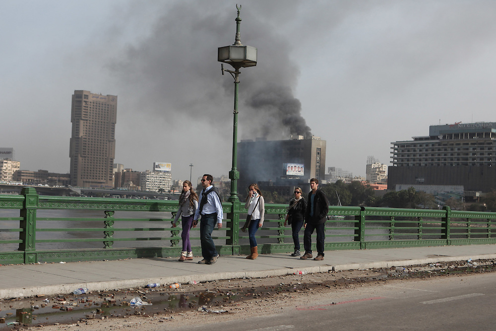 People walking in front of President Hosni Mubarak's National Democratic Party headquarters a day after it was set ablaze by protesters.