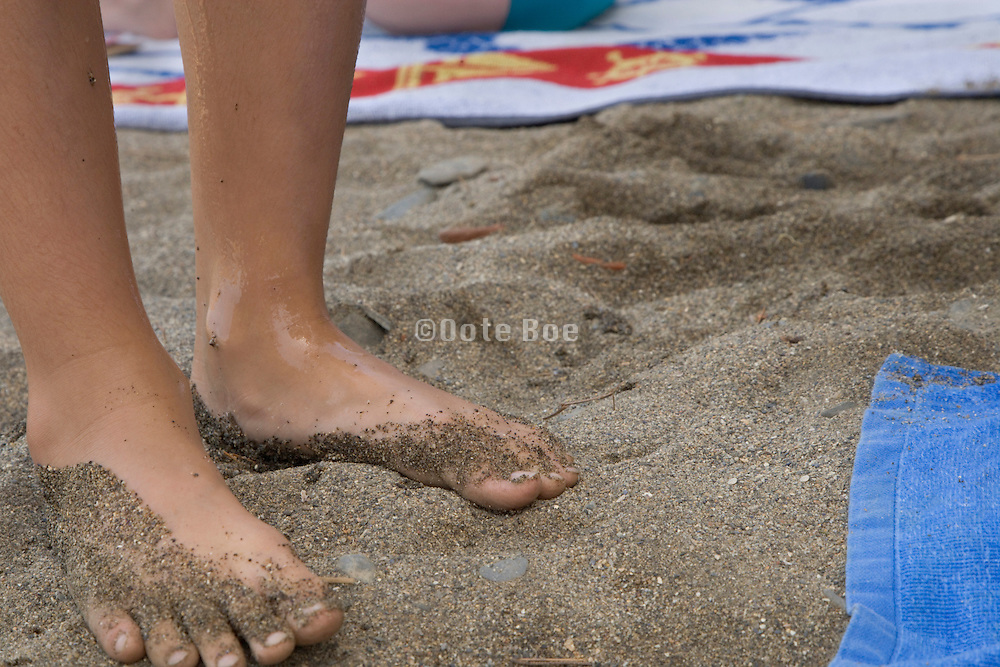 feet of a child with beach sand sticking to the skin