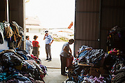 A woman collects clothing from piles of donations at a humanitarian center set up in the village of Naselje Dobor in Modrica, Bosnia and Herzegovina. <br /> <br /> Photo by Matt Lutton / Boreal Collective<br /> <br /> Flooding in Bosnia and Herzegovina.