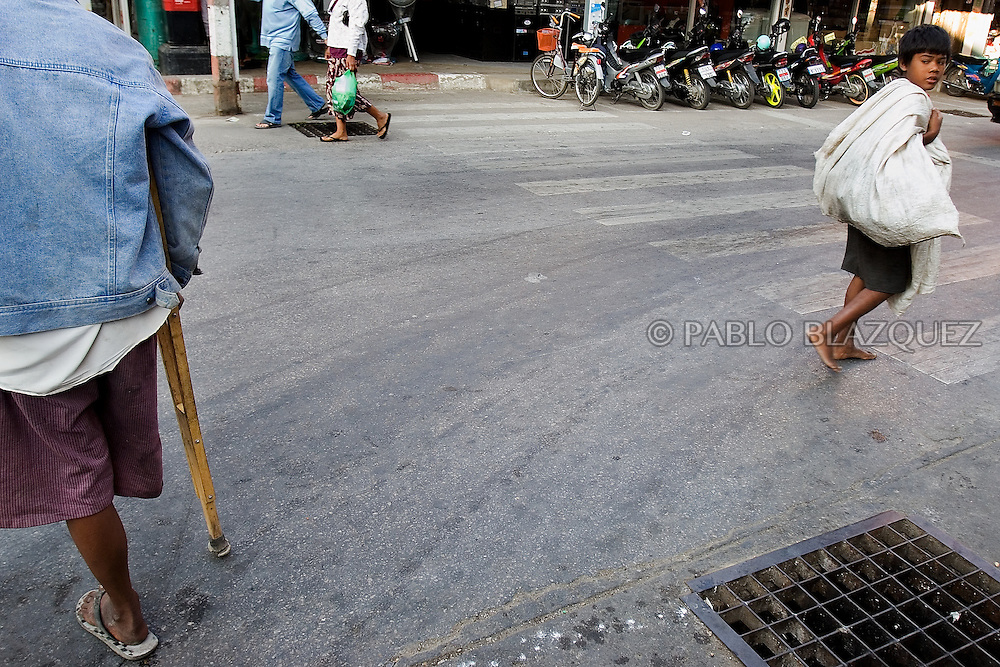 A scavenger child looks back at a one legged man in Mae Sot on December 21 of 2011, Thailand. .Many children on the border have lost their parents in Burma. When no body adopt them or a buddhist temple take care of them, they may become street children. Street children live from scavenging or begging. .Many Burmese people suffer from amputtations from land-mines placed by Burma army in an ongoing Civil War..Burma has since 1962 been ruled by dictator Burman Regimes. Pro democrats and minority ethnics have since been object of human rights abuses and armed minority groups has appeared bringing a state of Civil War..This situation makes every days people to flee their villages to go to Thailand.