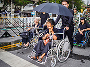 26 FEBRUARY 2017 - BANGKOK, THAILAND:  Thais in wheelchairs are helped into the Grand Palace to pay respects to the revered monarch. Thousands of Thais continue to line up at the Grand Palace in Bangkok daily to pay respects to Bhumibol Adulyadej, the Late King of Thailand, who died on 13 October 2016. The government set a year long mourning period for the revered King, who will be cremated in late 2017.       PHOTO BY JACK KURTZ