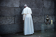 Pope Francis pauses to pray at the 'Death Wall' at the concentration camp Auschwitz.