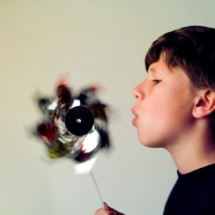 Wnd energy; boy blowing on pinwheel