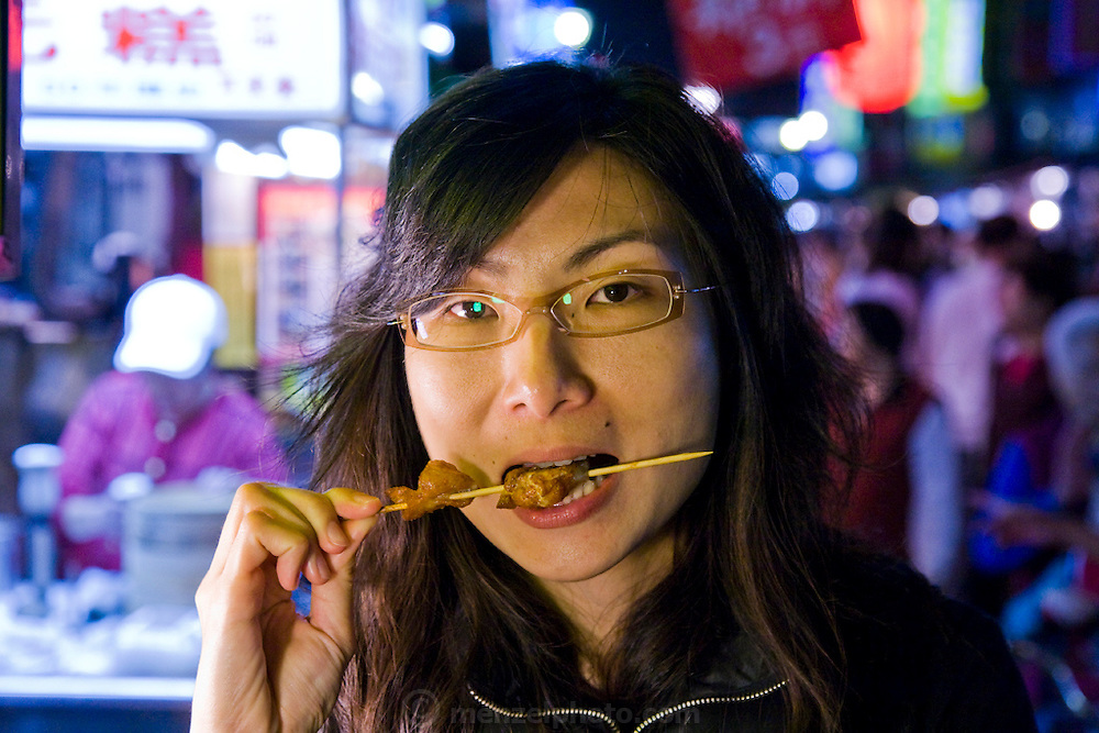 A woman takes a bite of a deep fried chicken anus on a stick at an open air food stall in Taipei, Taiwan.