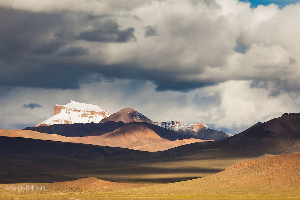 Storm clouds gather on the horizon just before sunset in the Sud Lipez range in southwestern Bolivia's Altiplano region near the town of San Pablo de Lipez.