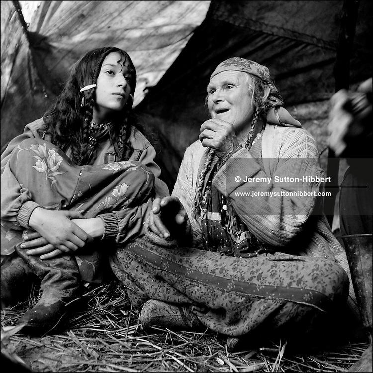 Talia Mihai, mother of the chief of Sintesti camp, tells stories to her grandaughter Garoafa, inside the family tent in the Kalderash Roma camp of Sintesti, near Bucharest. August 1994