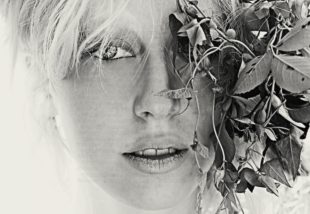 Close up of teenagers face with blonde hair behind foliage