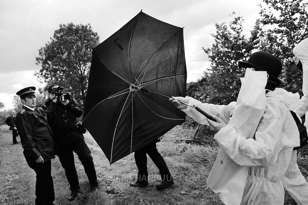 Climate activists from the Building Block, one of three groups of activists, are making their way across fields and pass police to join the ongoing blockade of Coryton oil refinery. The police Forward Intelligence Team has arrived and are photographing activists to identify them later. One way of rying to avoid being identified is using an umbrella to block the view...Crude Oil Awakening is a coalition of climate change activist groups. On Saturday Oct 16 they shut the only entrance to Coryton oil refinery in Essex, UK with the aim of highlighting the issues of climate change and the burning of fossil fuels. The blockade meant that a great number of trucks with oil were not able to leave the refinary during the day of action.
