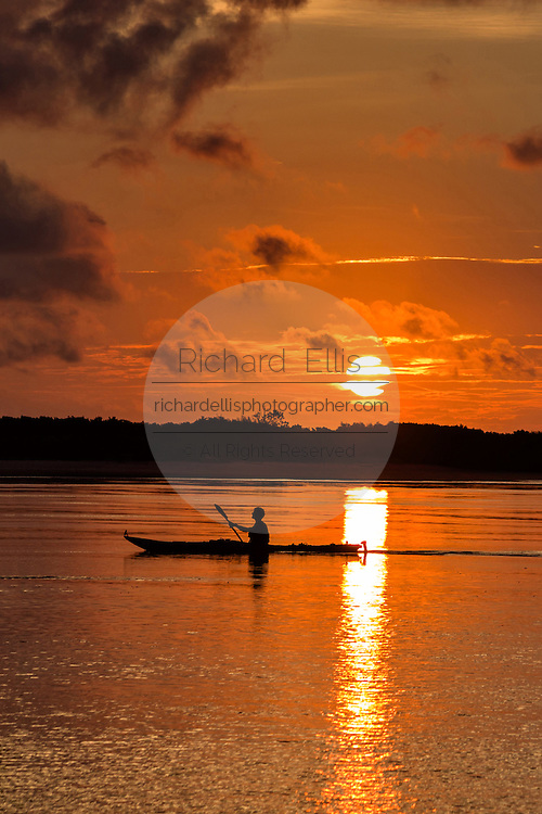 A lone kayaker silhouetted by sunrise at Isle of Palms beach at Wild Dunes near Charleston, South Carolina.