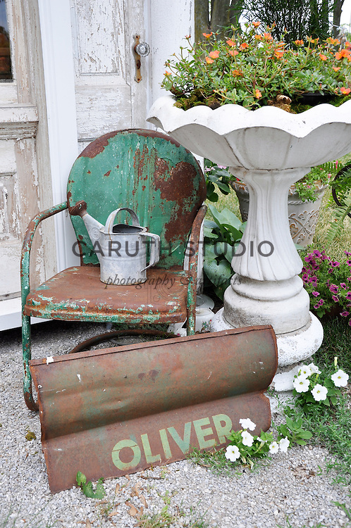 Architectural Salvage Shed: Vignette of birdbath, vintage metal motel chair, watering can