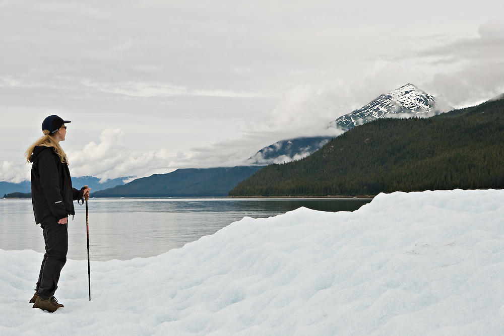 Woman standing on iceberg in Endicott arm in Southeast Alaska. Inside Passage. Summer. Afternoon. MR.