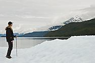 Woman standing on iceberg in Endicott arm in Southeast Alaska. Inside Passage. Summer. Afternoon. MR.
