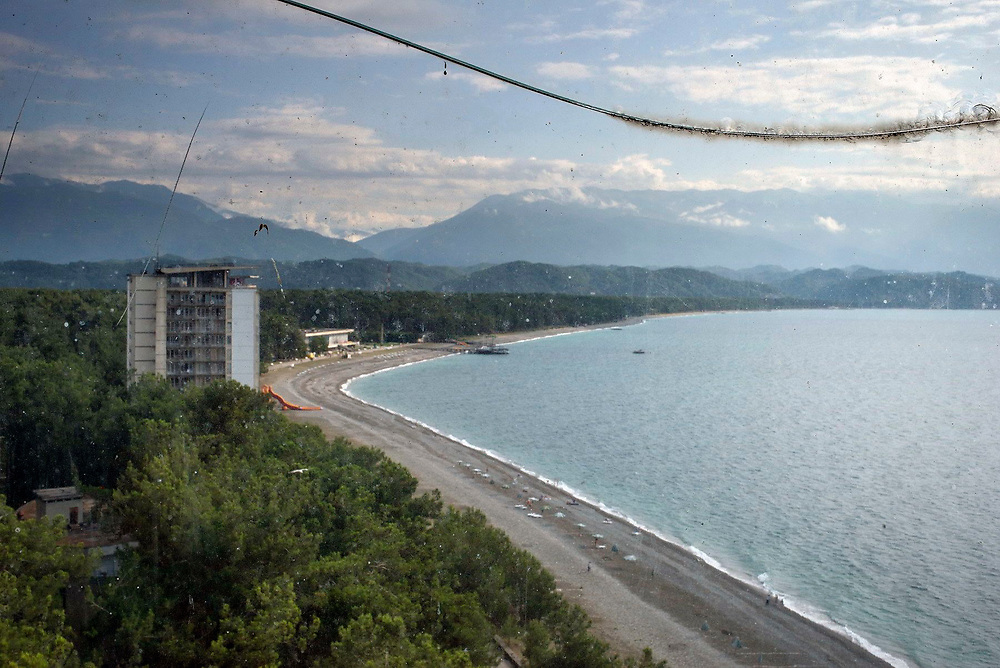 A view of the Black Sea beach in Pitsunda with mountains in the background seen through a broken window pane, Abkhazia