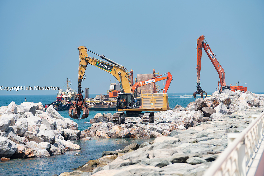Sea defence construction work by placed large stones on shore on The Palm Jumeirah island in Dubai , United Arab Emirates, UAE.