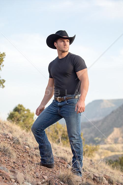 cowboy standing on a mountain range