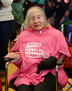 """Westbury, New York, USA. January 15, 2017. Sitting in wheelchair, PEARL BERGER, 97, of Amityville, who has breast cancer and Parkinson's Disease, has an """"I STAND WITH PLANNED PARENTHOOD"""" pink shirt draped on her chest, at the """"Our First Stand"""" Rally against Republicans repealing the Affordable Care Act, ACA, taking millions of people off health insurance, making massive cuts to Medicaid, and defunding Planned Parenthood."""