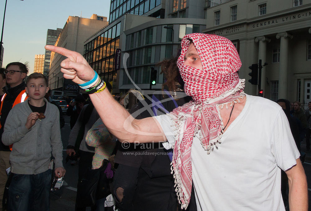 """London, March 7th 2015. Following the Climate march through London, masked anarchists and environmental activists clash with police following a breakaway protest at Shell House. PICTURED: A protester accuses a police officer of racism after he was told his scarf was """"dirty""""."""