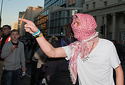 "London, March 7th 2015. Following the Climate march through London, masked anarchists and environmental activists clash with police following a breakaway protest at Shell House. PICTURED: A protester accuses a police officer of racism after he was told his scarf was ""dirty""."
