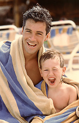 father and son under a big beach towel