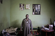 Egypt, Cairo: Kerlous, 44 years old, poses for a portrait inside his home. Kerlous  is a garbage collector. He collects Cairo's trash and recycle it inside Moqattam, the christian coptic quarter in Cairo where live 40.000 Zabbaleen (garbage collectors). ph.Christian Minelli.