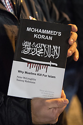 "© Licensed to London News Pictures . 03/11/2017 . Manchester , UK . A man holds up a copy of Mohammed's Koran by Peter McLoughlin and Tommy Robinson . Hundreds of fans of Tommy Robinson (real name Stephen Yaxley-Lennon ) queue up for books at the launch of the former EDL leader's book "" Mohammed's Koran "" at Castlefield Bowl . Originally planned as a ticket-only event at Bowlers Exhibition Centre , the launch was moved at short notice to a public location in the city . Photo credit : Joel Goodman/LNP"