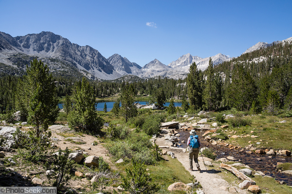A hiker follows Ruby Creek to Heart Lake, in scenic Little Lakes Valley, John Muir Wilderness, Inyo National Forest, Sierra Nevada, California, USA. Enjoy an easy, very rewarding hike from Mosquito Flat through Little Lakes Valley to Chickenfoot Lake and Gem Lakes. To reach the trailhead, turn off Highway 395 at Toms Place (15 miles south of Mammoth Junction) onto paved Rock Creek Road, and drive 10.5 miles to the end. We hiked the moderate trail to Morgan Pass, 7.5 miles round trip with 1250 feet cumulative gain; but you should skip the left turn to redundant Morgan Pass and instead turn right to visit the pretty Gem Lakes.