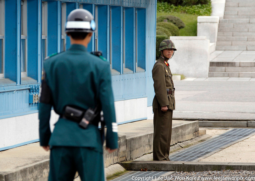 A North Korean soldier (R) watches south as a South Korean soldier stands guard, between at the concrete border separating the two Koreas at the truce village of Panmunjom in the demilitarized zone in Paju, north of Seoul. Photo by Lee Jae-Won (SOUTH KOREA) www.leejaewonpix.com/