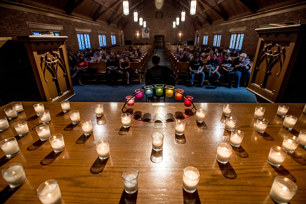 "LYNCHBURG, VA - June 12: 49 candles, one for each victim, along with an arch of rainbow candles illuminate the alter of First Christian Church as Roger Scott leads attendees in singing ""Somewhere Over the Rainbow"" during a vigil for the anniversary of the Pulse nightclub shooting in Orlando on Monday, June 12, 2017 in Lynchburg, Va. About 60 Lynchburgers paid their respects at a service led by clergy from different faiths and churches in the area. 49 paper doves were handed out, each with a name of a victim, and as victims' names were read people with the corresponding paper dove stood. A rainbow flag, which had hung on the roadside sign for The First Christian Church since the tragedy last year, was stolen over the weekend and replaced with an American Flag with the words ""Levticus 18:22"" written on it. Rev. Cowgill said the church replaced that flag with new flags, one rainbow and one American flag. (Photo by Jay Westcott/The News & Advance)"