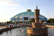 """Low angle view of fountain with the Circus, 1976, renovated 1999, in the background, Tashkent, Uzbekistan, pictured on July 3, 2010, in the afternoon. People splash happily in the pool around the fountain near the State Circus. Tashkent's first permanent circus, built in 1919, was destroyed in 1966 by an earthquake and replaced by the current circus in 1976.  Since the demise of the Soviet Union the Uzbek State Circus has successfully toured the world. Tashkent, 2000 year old capital city of Uzbekistan, a Silk Road city whose name means """"Stone Fortress"""", is now very modern due to a disastrous earthquake in 1966, after which it was greatly rebuilt. However, some of the old buildings still stand in the glittering modern city. Picture by Manuel Cohen."""