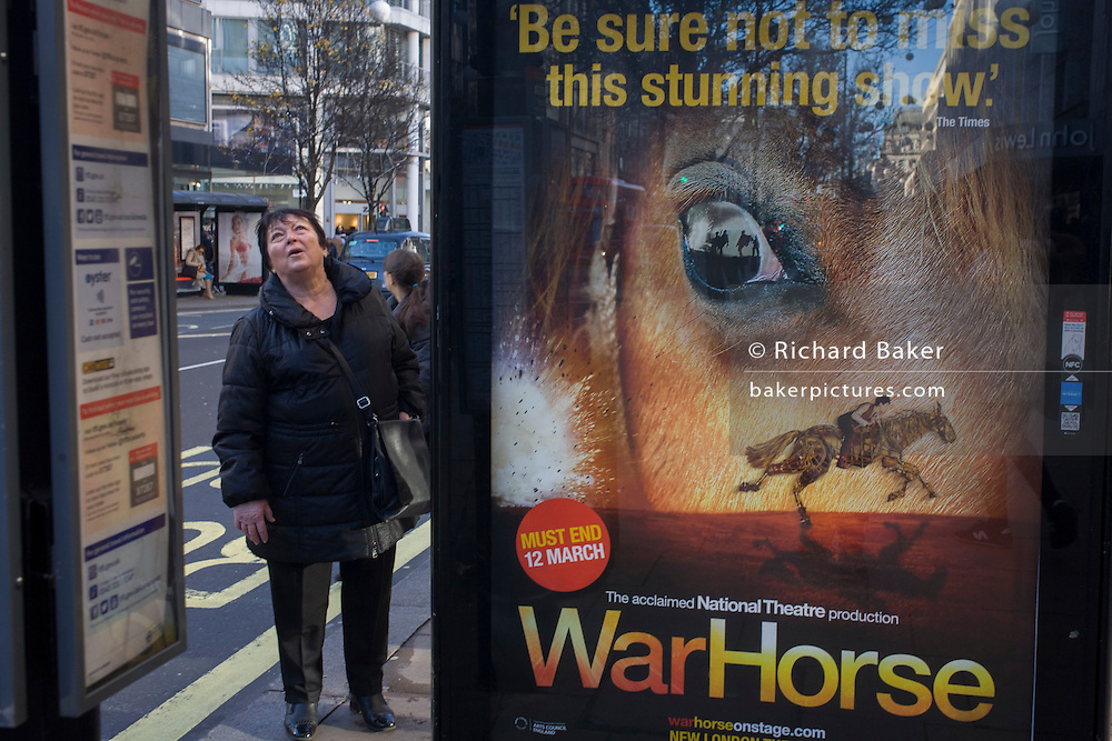 Woman shopper at a bus stop with a War Horse poster in central London