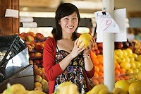 Portrait of young woman holding fruit in market