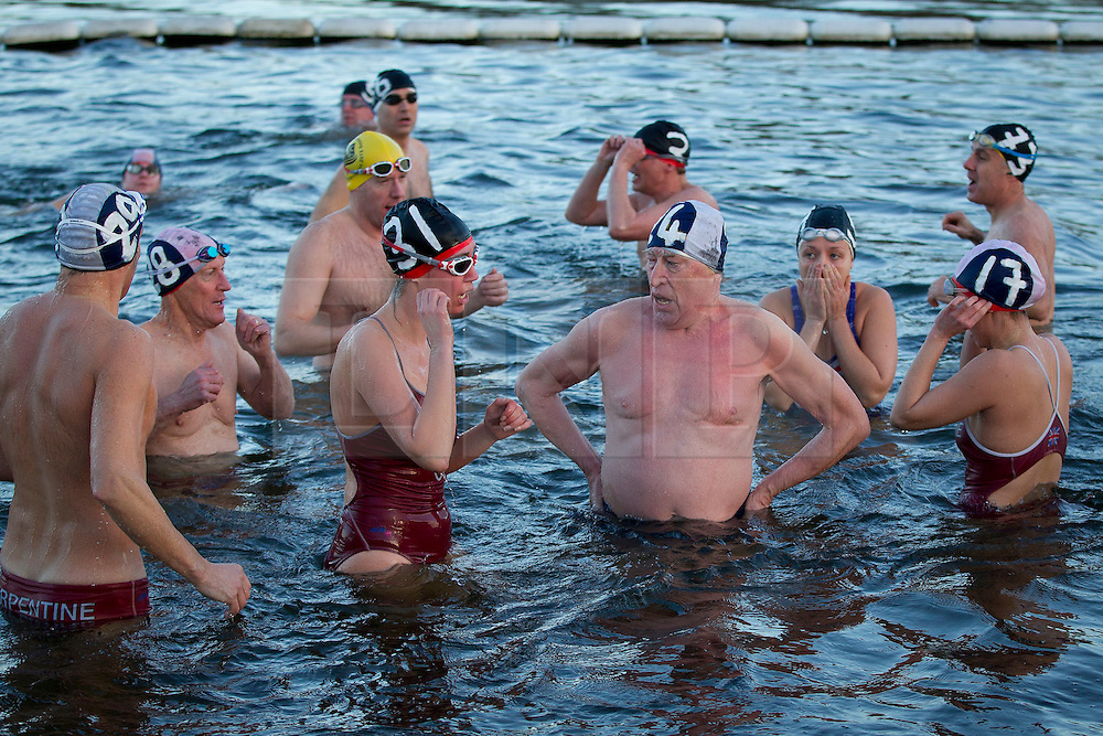 © Licensed to London News Pictures. 25/12/2013. London, UK. Members of the Serpentine Swimming Club pause after completing the Serpentine Swimming Club's annual Christmas morning 'Peter Pan Cup' race in Hyde Park, London, today (25/12/2013). The race, which takes place every Christmas Day on the Serpentine River, takes its name from from the novel by J.M.Barrie after the author presented the first Peter Pan Cup in 1904. Photo credit: Matt Cetti-Roberts/LNP