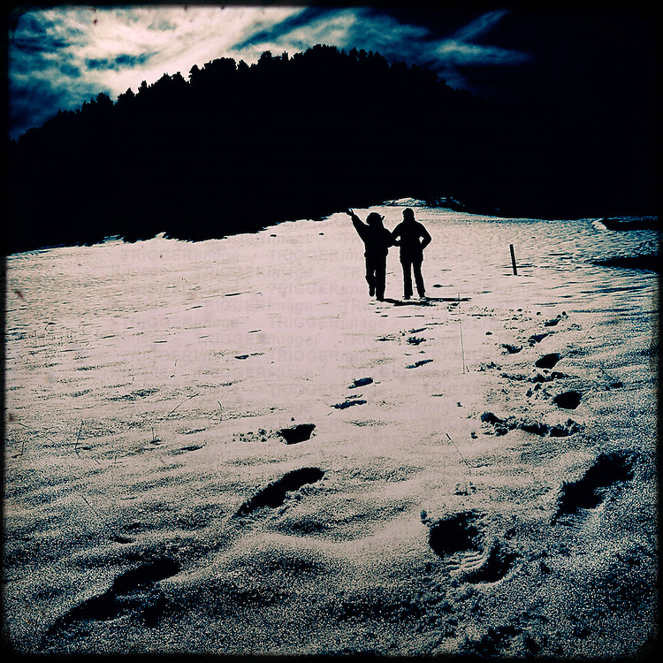 Two people walking in snow leaving foot prints