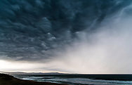 Fast-moving, dark and dramatic clouds sweep across Monterey Bay, California