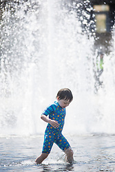 © Licensed to London News Pictures. 30/06/2015. Bradford UK.  A child cool's off in the water fountains at Centenary square in Bradford. Britain is set to sizzle in temperatures of up to 34C (93F) today, with forecasters predicting the hottest day for several years. A tropical air mass moving from North Africa, Spain and Portugal means that we could be hotter than Rio de Janeiro. Photo credit : Andrew McCaren/LNP