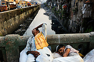 Tired porters taking a break at dusk, on a bridge over a polluted canal crossing Dharavi, Mumbai's biggest slum, a thriving mix of poverty and enterprise, a city within the city.