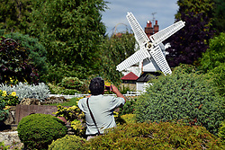 © Licensed to London News Pictures. 29/08/2013. Beaconsfield, UK A man photographs a windmill. People enjoy the sunshine and hot weather at Bekonscot Model Village in Berkshire today 29th August 2013. Bekonscot Model Village and Railway is the world's oldest and original model village, opening for the first time in 1929. With over 80 years of history, huge model railway, 1.5 acres of well kept gardens and finely detailed model buildings. Photo credit : Stephen Simpson/LNP