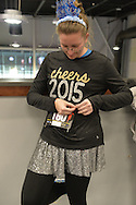 East Meadow, New York, USA. December 31, 2014. LAURA SOFTY, of Bethpage, pins on her race bib identification, in preparation for participating in a 5K New Year's Eve DASH to support the Long Island Council on Alcoholism and Drug Dependence (LICADD) at the Twin RInks Ice Center at Eisenhower Park in Long Island. Softy is a member of Greater Long Island Running Club (GLIRC). A Skatin' New Year's Eve event started hours earlier and a New Year's Eve Party, open to runners, family and friends continued until 2:30 a.m.