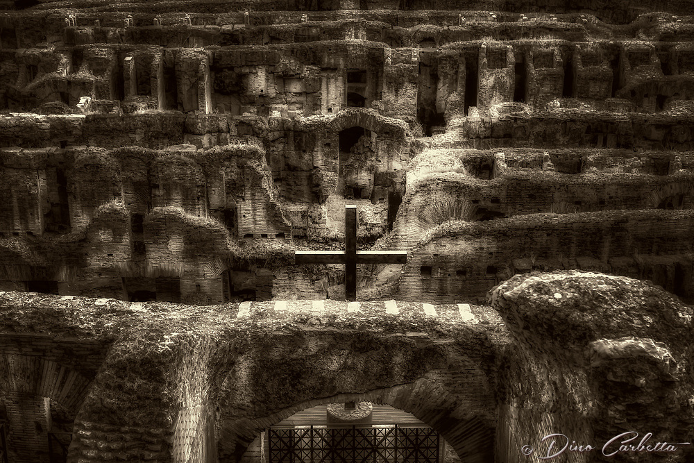 """""""The Holy Cross blesses the Christian martyrs of the Roman Coliseum - BW""""…<br /> <br /> This is one of the most poignant and meaningful images of my entire Italian journey. The Holy Cross stands very majestic as evening descends on the ancient ruins.  The Colosseum has close connections with the Roman Catholic Church, as each Good Friday the Pope leads a torch lit """"Way of the Cross"""" procession that starts in the area around the Colosseum.  The Colosseum is generally regarded by Christians as a site of the martyrdom of large numbers of believers during the persecution of Christians in the Roman Empire, as evidenced by Church history and tradition.  A Cross stands exultant in the Colosseum center with a plaque, stating:  """"The amphitheatre, one consecrated to triumphs, entertainments, and the impious worship of pagan gods, is now dedicated to the sufferings of the martyrs purified from impious superstitions.""""  Viewing the iconic Colosseum for the first time…I was in awe.  It is as grand in person as it appears in the media, and it seems to hold a very mystical aura.  Climbing the ancient steps inside, one cannot help but feel not only the suffering of its past, but the forgiveness and sacrifice of its present stature."""