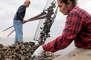 Crystal Goggins, 37, culls freshly-harvested oysters that her boyfriend Billy-Jack Foley, 34, tongs out of Apalachicola Bay. Goggins is a second-generation oyster harvester, who ended up in Eastpoint, Fla. after her mom followed a man there with the promise of a place that she could always provide for her family in; Foley is a fourth-generation oysterman who got out briefly after some college and a job on land working in the prison system, but was ultimately called back to the water as a way of life by the allure of freedom and money.