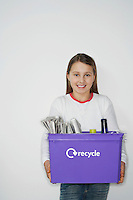 Girl (10-12) holding recycling container smiling