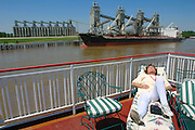 The Mississippi Queen paddlewheeler passing a Japanese owned grain silo while a pasenger enjoys a nap.
