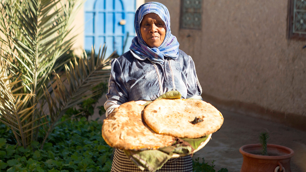 Lady prepares madfouna - the Berber pizza - at a earthen home in Hassilabied village, Southern Morocco, 2017-12-21.