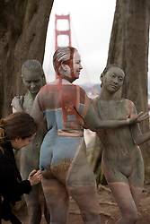 Trina Merry, left, a painter originally from San Jose, Calif. who now lives in New York, paints a trio of nude models in front of the Golden Gate Bridge to promote positive body image and respect for the fine art nude, Thursday, July 9, 2015, in San Francisco, Calif. (Photo by D. Ross Cameron)