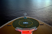 A crew member meditates on the helipad on the stern of the cruise ship Oasis of the Seas. The ship, currently the largest in the world, is owned by Royal Carribean Cruise Line.