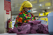 A fire extinguisher behind a garment worker at work on a machine inside  Epyllion Group garment factory in Bangladesh.