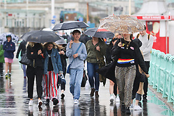 © Licensed to London News Pictures. 22/06/2015. Brighton, UK. People take shelter under their umbrella's as rain showers hit Brighton, today June 22nd 2015. Photo credit : Hugo Michiels/LNP