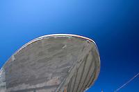 Profilo dello scafo di una paranza in restauro nella darsena del porto di Gallipoli (LE) che si staglia sul cielo terso